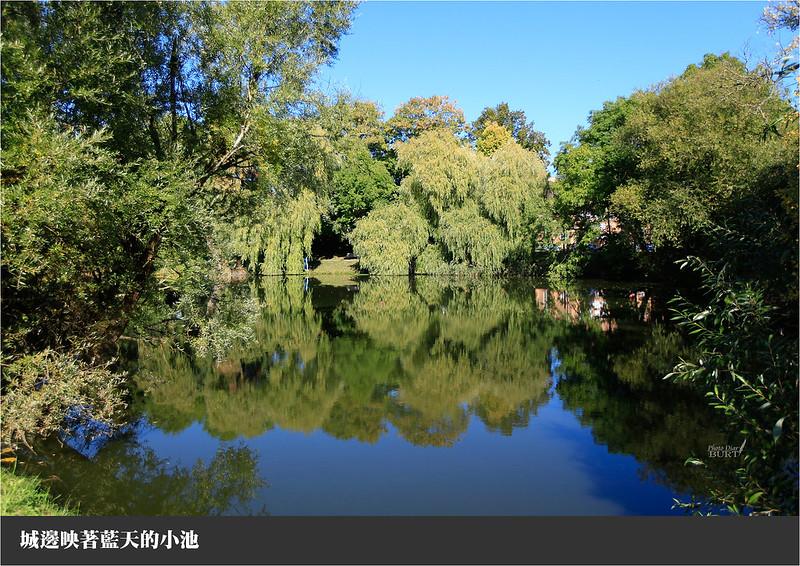城邊映著藍天的小池