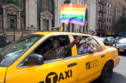 A man waving a rainbow flag out a cab