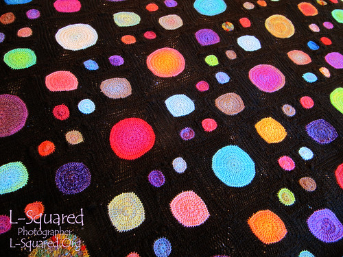 crocheted blanket that has lots of colorful dots (small, medium and large) scattered randomly over a brown background.