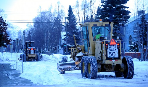 Stay back 50ft, snow removal with snow grators, 6 wheeled tractors plowing snow from city streets, cloudy day, mid-winter, Anchorage, Alaska, USA by Wonderlane