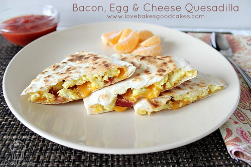 Bacon Egg and Cheese Quesadilla cut and stacked on plate with orange slices.