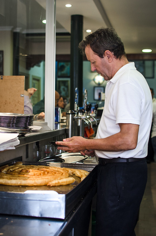 A waiter at La Centuria Cafe in Sevilla, Spain, prepares freshly fried churros.