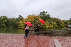 A woman trying various poses with her umbrella at the Bethesda Terrace in Central Park.
