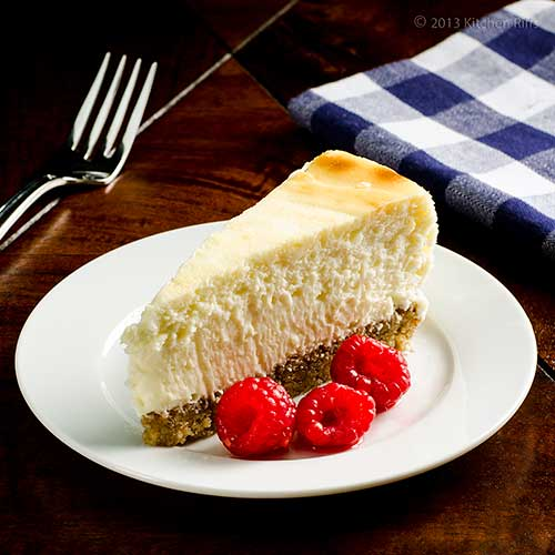 Lemon Cheesecake with Walnut Crust, on plate with raspberry garnish