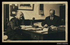 Photographic postcard of a man and a woman seated at a partners desk