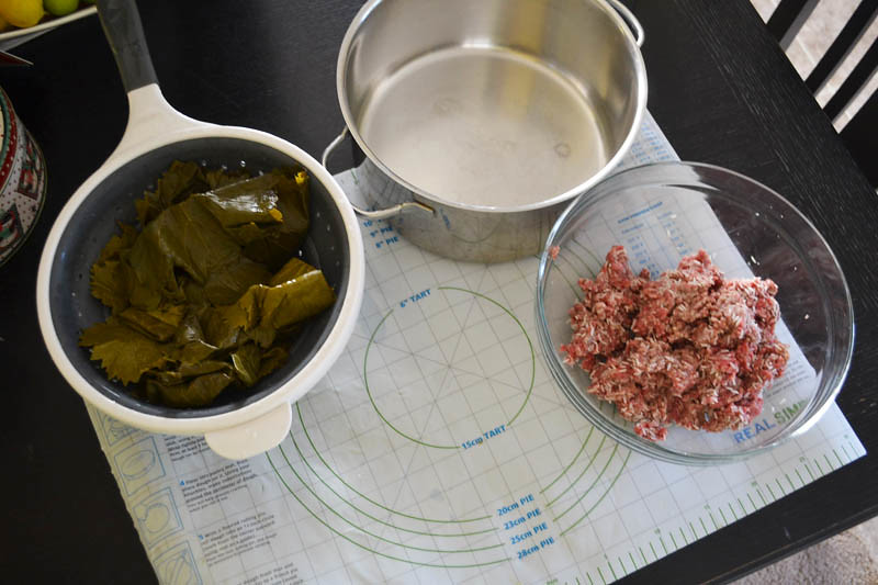 Before ,aking stuffed grape leaves, have an assemply line in place to make rolling faster and more efficient, with 1 bowl of the meat mixture and the pot to lay the stuffed grape leaves in.