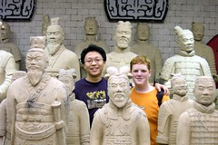 Mark Berninger '05  and host brother Jihun standing behind terracotta soldiers, Xi'an China - 2004