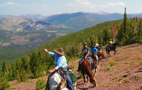 "Joni Packard, U.S Forest Service, points out a landscape feature to a group of students on horseback as they ride in the Scapegoat Wilderness area during the filming of ""Untrammeled.""  The youth learned about the history of the Wilderness Act and the important legacy and heritage of wilderness that is now theirs. (U.S. Forest Service)"