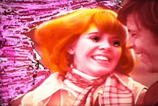 A still from Dinorah's film, with an orange and pink model whose eyes are whited out