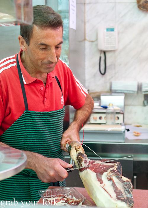 Slicing Jamon Iberico puro de bellota at Mercado de la Cebada in Madrid, Spain