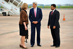 U.S. Secretary of State John Kerry stands with Embassy Delhi Chargé d'Affaires Kathleen Stephens and Ministry of External Affairs Joint Secretary of Americas Division Vikram Doraiswamy after arriving at Palam Air Force Base in New Delhi, India, on July 30, 2014, for a Strategic Dialogue with Commerce Secretary Penny Pritzer. [State Department photo/ Public Domain]