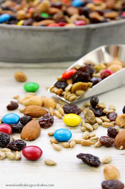 Sweet & Salty Trail Mix in a scoop and poured out on a table.