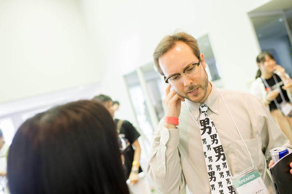 写真:休憩中にスタッフと歓談する、「男」の漢字がプリントされたネクタイをしたブレットさん