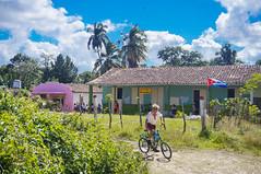 A kid bikes home from school at Vega de Palma, Cuba