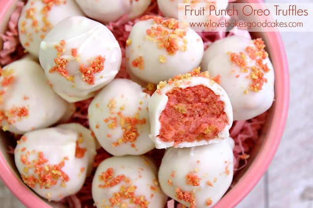 Fruit Punch Oreo Truffles in a bowl with a bite removed from one to show inside.