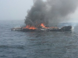 The 25-foot pleasure craft Dawn Trader is engulfed in flames following an engine fire three miles north of Neah Bay, Wash., Aug. 3, 2014. A Coast Guard MH-65 Dolphin helicopter crew from Air Station Port Angeles safely hoisted the vessel operator from his life raft and transported him to a nearby hospital. (U.S. Coast Guard photo courtesy of Coast Guard Station Neah Bay)
