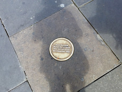 Golden circular plaque on pavement in Newcastle