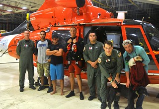An Air Station/Sector Corpus Christi MH-65 Dolphin helicopter crew stands with three men and two dogs they picked up from Padre Island National Seashore in Texas Wednesday, Aug. 27, 2014. A man with two dogs got his vehicle stuck and two other men got their jeep stuck trying to help him. (U.S. Coast Guard photo by Air Station Corpus Christi)