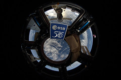 Patch celebrating 50 years of European cooperation in space floating in the Cupola of the ISS