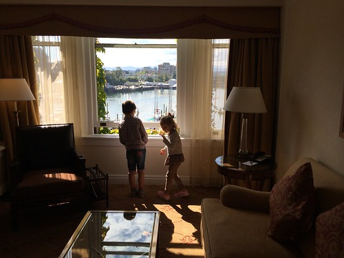 Kids looking out of the window in the living room at Fairmont The Empress, Victoria, BC