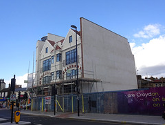 Two terraced white-painted buildings with brick detailing and scaffolding over the lower floors.  The side wall of the pair is tall and blank, and behind the ground-floor hoardings there's a large empty space visible next to it.