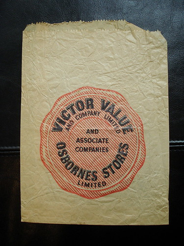 "A brown paper bag with a large stylised red seal printed on it, including the words ""Victor Value and Company Limited / and Associate Companies / Osbornes Stores Limited""."