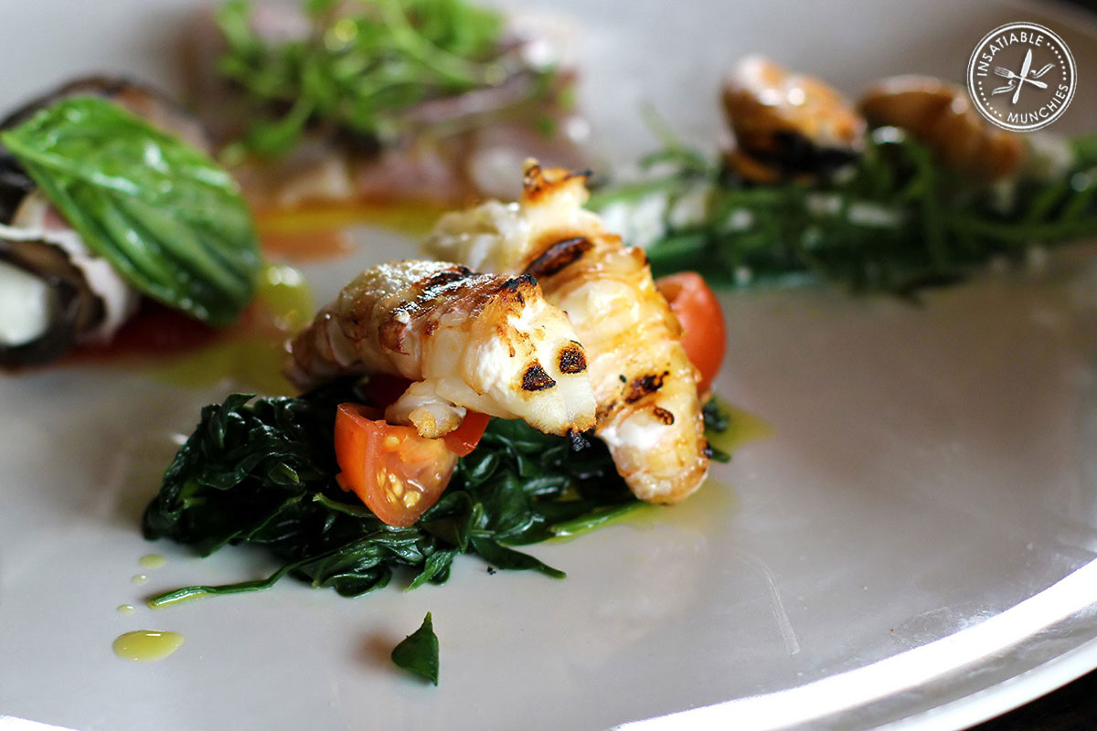 Balmain bugs are grilled to perfection, and served on a bed of wilted spinach and fresh cherry tomatoes.