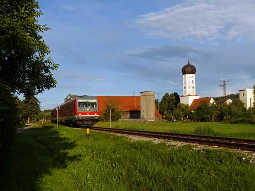 In der Nähe des heutigen Streckenendes präsentiert sich der Triebwagen im Abendlicht vor der Ortskulisse von Jebertshausen.