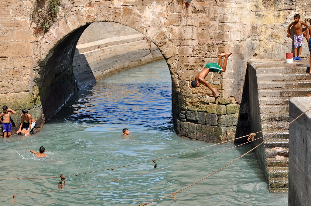 ESSAOUIRA - SEPTEMBER 29: Children take a bath in the canal. Essaouira, Morocco, September 29, 2013.