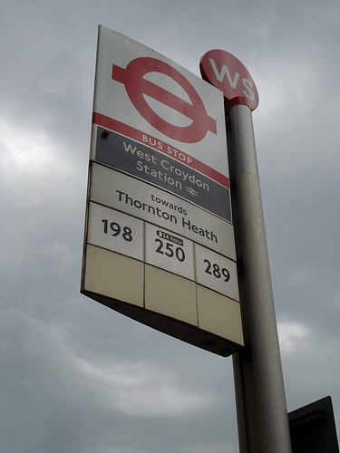 """A bus stop sign reading """"West Croydon Station towards Thornton Heath"""", with bus numbers """"198"""", """"250"""", and """"289"""" underneath.  The sky is grey and cloudy."""