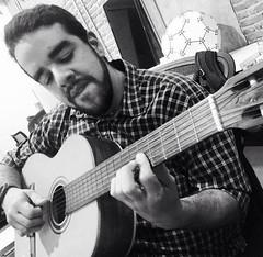 bassist(0.0), slide guitar(0.0), bass guitar(0.0), string instrument(1.0), musician(1.0), music(1.0), acoustic guitar(1.0), monochrome photography(1.0), guitarist(1.0), guitar(1.0), jazz guitarist(1.0), monochrome(1.0), black-and-white(1.0), person(1.0), black(1.0), string instrument(1.0),
