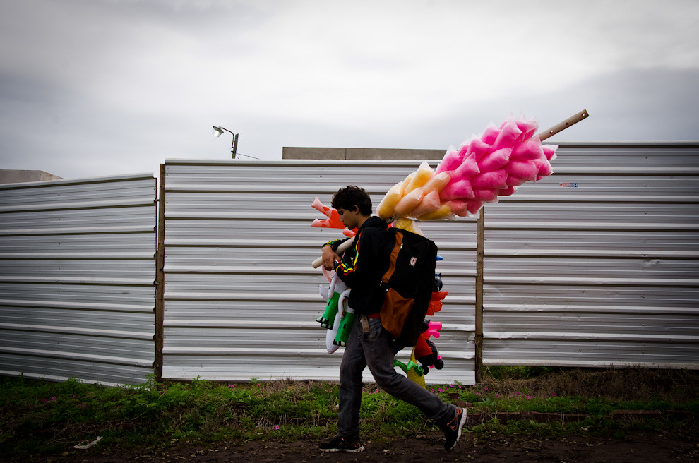 Un joven vendedor de juguetes y algodón de azúcar camina rumbo a un terreno en busca de clientes, donde se llevaría a cabo una Jineteada por el día de San Juan, en la ciudad de San Juan, departamento de Misiones. (Elton Núñez)