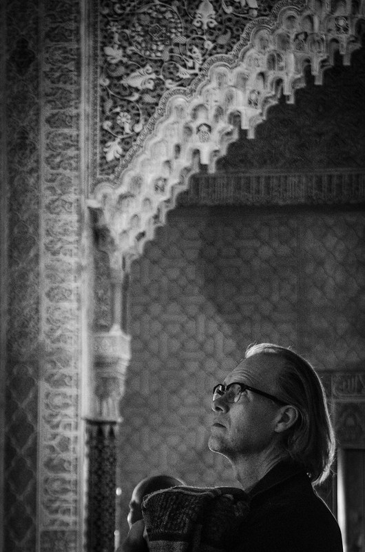 A visitor at the Alhambra contemplates the intricate Moorish carvings inside the Nasrid Palaces.