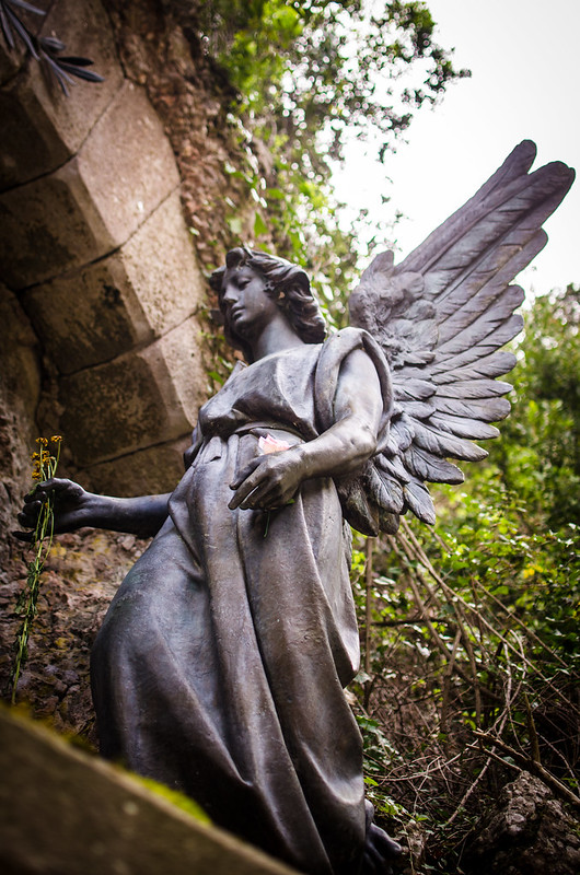 Visitors place fresh flowers in the hand of an angel statue at Montserrat, Spain.