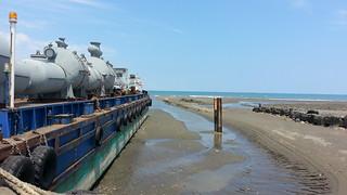 接駁船與右方黑色零星礁體;圖片提供:桃園在地聯盟。