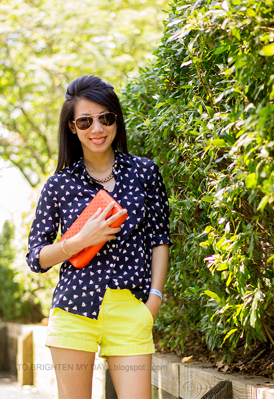 printed silk blouse, yellow shorts, orange clutch