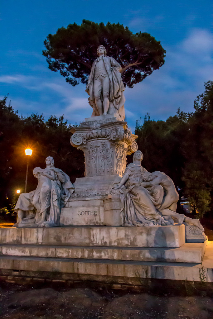 "Monument to Goethe by Gustav Eberlein; the poet is shown standing on a colossal Corinthian capital and is surrounded by statues portraying characters of his works Iphigenia in Tauris, Mignon and Faust.  ""Donated to Italy in 1903 by Emperor William II of Germany, the monument was created by German sculptor Gustav Eberlein (1847-1926) and is located on the avenue dedicated to Goethe on the corner of Viale S Paolo del Brasile. In Eberlein's sculpture Goethe is depicted standing on a large Corinthian base, surrounded by statues portraying characters from his writings. A demonic figure from German folklore, Mephistopheles originally appeared in literature as the demon in the Faust legend, and later featured in the work of Goethe. """