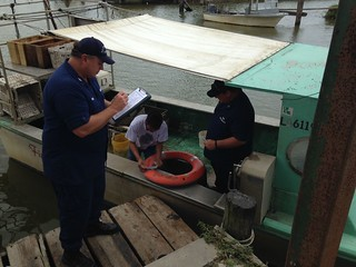 A member from the Coast Guard Auxiliary provides a free safety exam for a commercial fishing vessel. The Coast Guard Auxiliary provides free, no fine safety examinations of commercial fishing vessels in order to promote safe boating. (U.S. Coast Guard photo courtesy of Coast Guard Marine Safety Unit Morgan City)