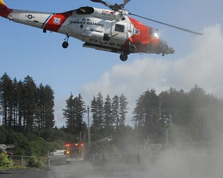 The crew of an Air Station Kodiak MH-60 Jayhawk helicopter and Kodiak Fire Department personnel depart after completing a medevac of an injured woman in Kodiak, Alaska, Aug. 1, 2014. Due to the nature of the injuries and the remote location of the accident, the Coast Guard assisted Kodiak Police Department in safely transporting the woman to emergency medical services. (U.S. Coast Guard photo by Auxiliarist Tracey Mertens.)