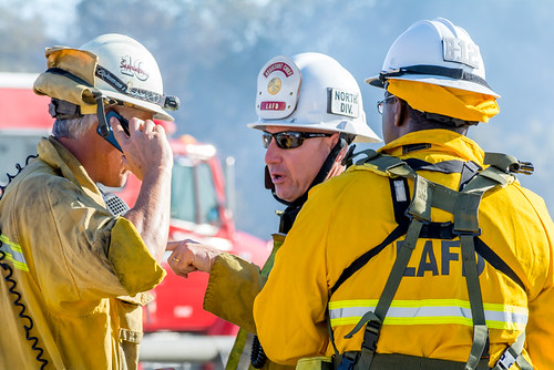 Three LAFD Chiefs, wearing brush firefighting gear, speaking to one another regarding the active fire.