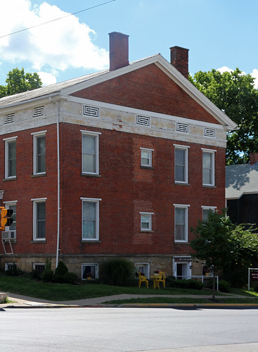 house dwelling residence historic greek revival brick twostory stone foundation 11 windows entablature frieze architrave vents frets grilles chimneys gable sidewalk chairs street bushes sky blue clouds mount vernon ohio knox county mtvernon
