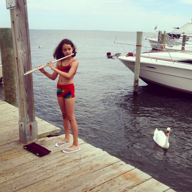 A teenage girl in a rainbow outfit serenades swans with her flute in Cherry Grove.