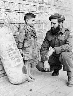 Private J.S.P. Bowen of Princess Patricia's Canadian Light Infantry saying goodbye to a young friend...  Italy, 1944 / Le soldat J.S.P. Bowen du Princess Patricia's Canadian Light Infantry salue son jeune ami... Italie, 1944