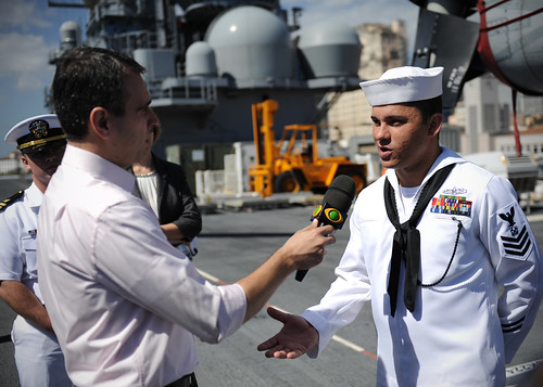 Boatswain's Mate 1st Class Tiago Campos, from Brazil, assigned to USS America, answers questions during a media interview