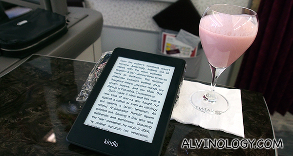 Enjoying reading on my Kindle while sipping a glass of strawberry yoghurt