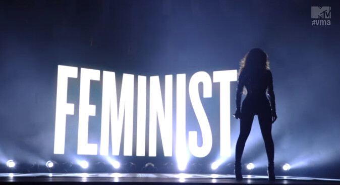 "Beyonce in shadow in front of glowing ""Feminist"" sign"