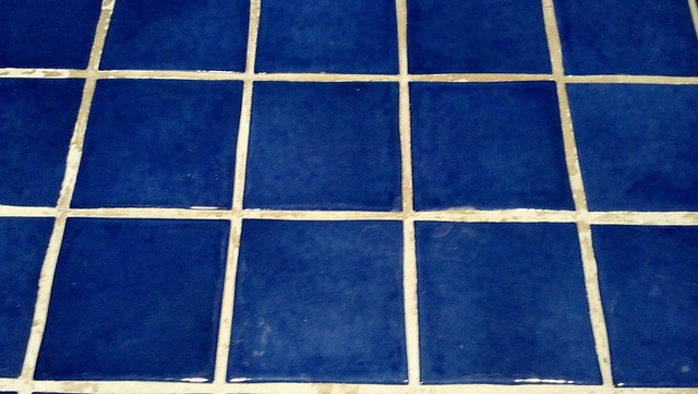 Blue tile floor with grout stains before treatment with Groutshield colorseal.