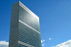 The United Nations Headquarters building in New York City glistens in the late-afternoon sun on September 22, 2014, as delegates arrive in town for the annual General Assembly meeting. [State Department photo/ Public Domain]