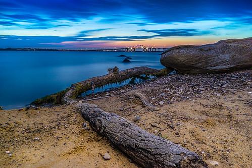wood longexposure bridge sunset lake water sand rocks texas