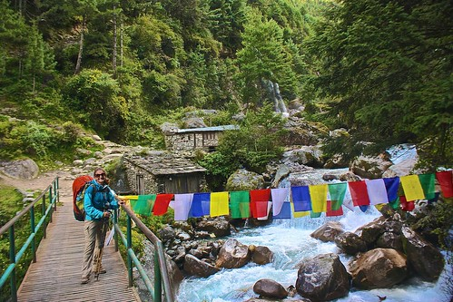 Lina poses by the prayer flags over a creamy blue river. small waterfall in the background